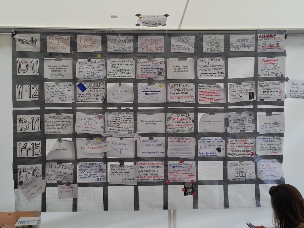 programmet för fredagens sessions i form av papperslappar tejpade på ett stort schema på tältväggen