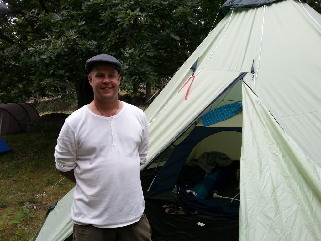 Peter Söderman poserar framför tältet