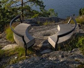 två rundade bänkar på en klippa vid havet